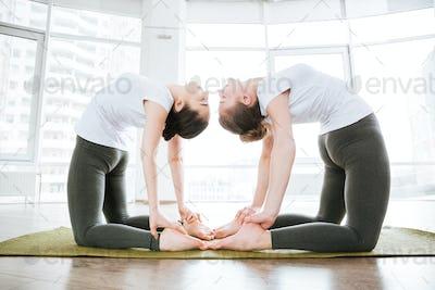Two women stretching legs on green mat in studio