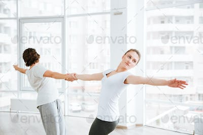 Beautiful young woman practicing yoga with partner in studio