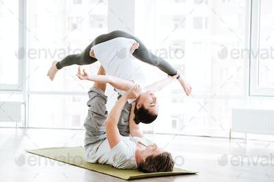 Couple doing flexibility workout in yoga studio