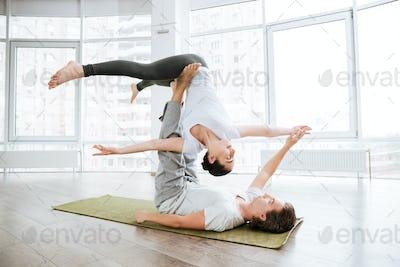 Beautiful couple doing acro yoga exercises in studio together