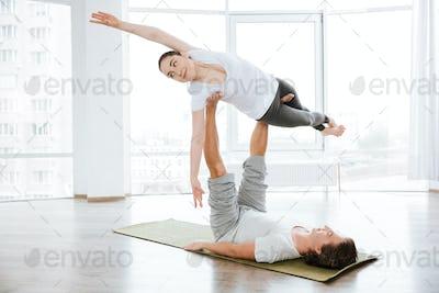 Beautiful woman balancing doing acro yoga with partner in studio