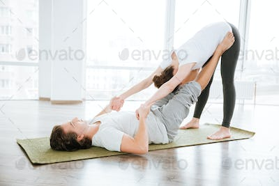 Beautiful couple doing relaxation exercises in studio together