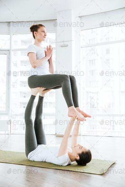 Two young women doing acro yoga exercises