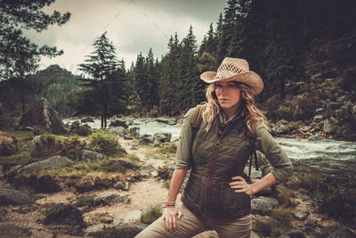 Beautiful woman hiker standing near wild mountain river.