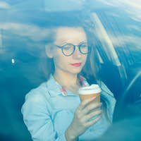 Businesswoman sending a text message and drinking coffee while d
