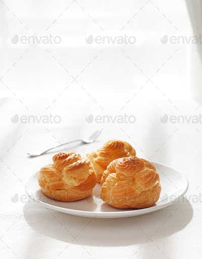 Profiteroles, choux with a custard cream, creme anglaise, whipped cream, dessert on a white plate