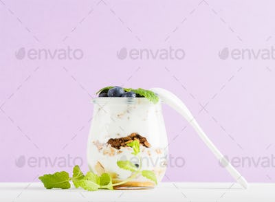 Yogurt oat granola with jam, blueberries and green leaves in glass jar on pastel lilac backdrop.