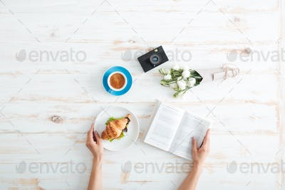 Hands of woman eating croissant with coffee and reading book