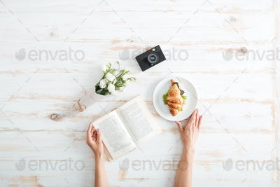 Female hands holding book on the wooden desk