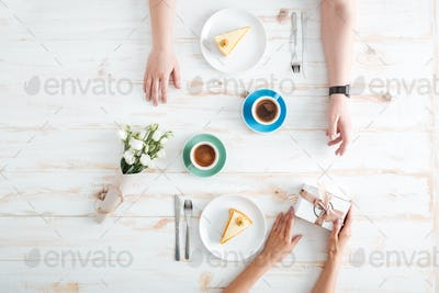 Hands of woman giving present to man on wooden table