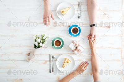 Top view of couple eating dessert and holding hands