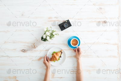 Hands of woman drinking coffee with croissant on wooden table