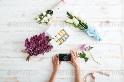 Hands of young woman holding photo camera on wooden table