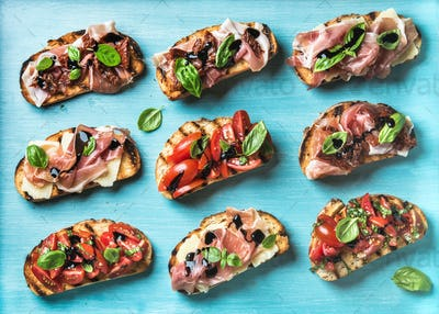Brushetta snacks for wine. Variety of small sandwiches on turquoise blue backdrop