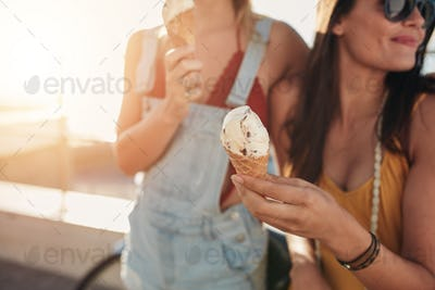 Ice cream in hand of a woman standing with her friend