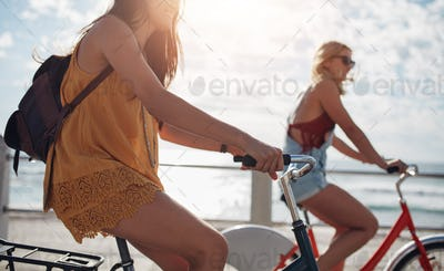 Two young female cycling outdoors on a sunny day