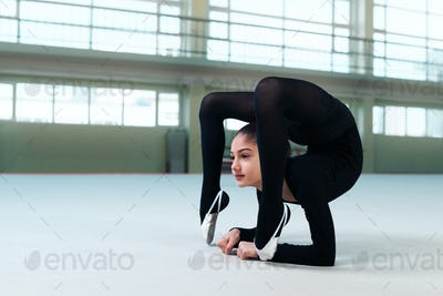 gymnast performs a back bend on  floor