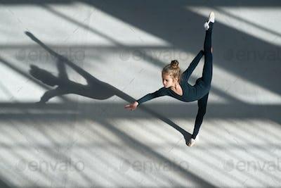little girl doing balance on  rhythmic gymnastics
