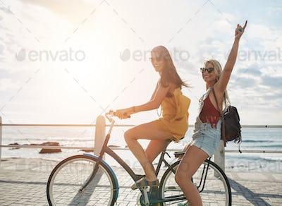 Happy young women enjoying bike ride