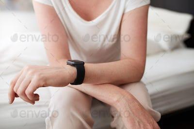 Woman sitting on bed wearing a wrist watch