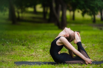 Young woman doing gymnastics yoga and stretching in the city park on sunset