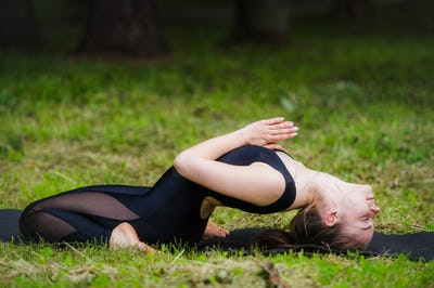 Young woman doing Yoga, reclining spinal twist position