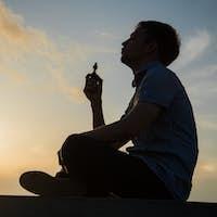 Man smoking vaping e-cigarette vape box mode over golden sunset
