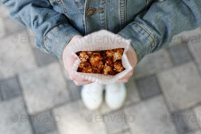 Child with popcorn in hands top view, POV