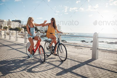 Best friends riding cycles on the seaside promenade