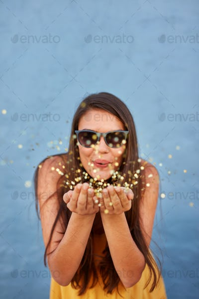 Happy young woman blowing confetti in the air
