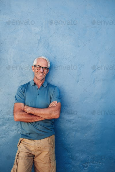 Smiling mature man standing with his arms crossed
