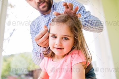Hipster father with his daughter, styling her hair, indoors