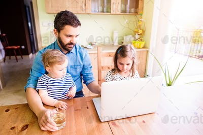 Father and daughters, playing on laptop, sitting in kitchen