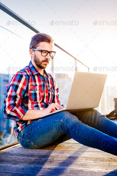 Businessman working from home on laptop, sitting on balcony