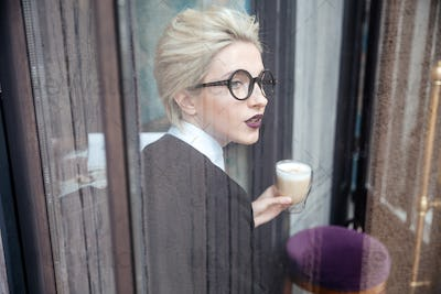 Portrait of a stylish young woman with cup in cafe
