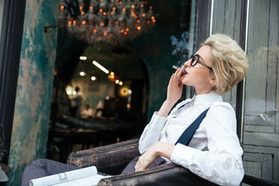 Relaxed young woman smoking cigarette in cafe