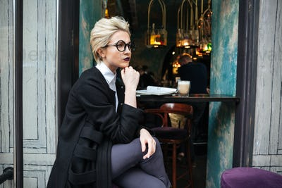 Portrait of stylish woman sitting in cafe alone