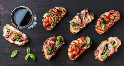 Brushetta snacks for wine. Variety of small sandwiches on dark rustic wooden backdrop