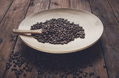 Coffee beans in bowl with wooden spoon on table