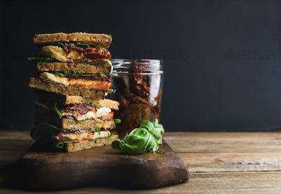 Caprese sandwich or panini. Whole grain bread, mozzarella, cherry and dried tomatoes, basil