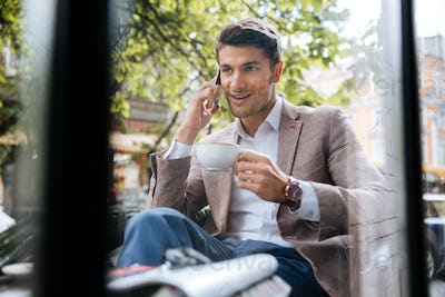 Man talking on mobile phone and drinking coffee in cafe