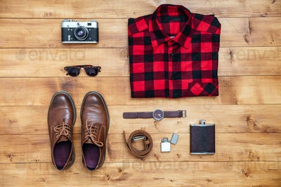 Travel concept shirt, camera, shoes, flask, watch, shoes on desk