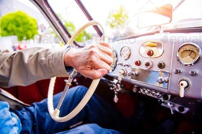 Close up unrecognizable man driving a veteran car