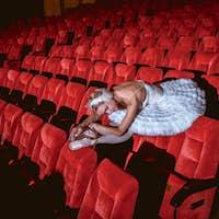 Ballerina sitting in the empty auditorium theater