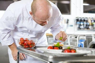 Chef decorates dessert cake with strawberry in kitchen