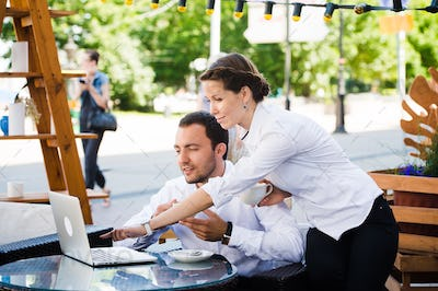 man and woman working on laptop at outdoors cafe during the break
