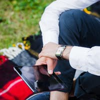 Young business man using tablet in a park. Close-up shot.