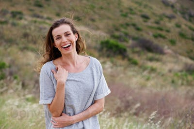 Healthy laughing woman standing in field outside