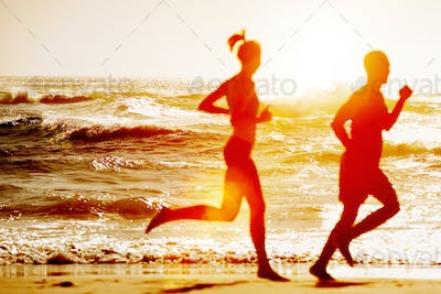Silhouette of two running at the beach