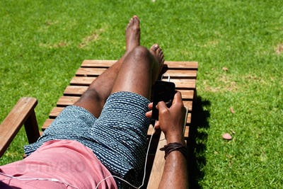 Man relaxing on lounge chair with a cell phone